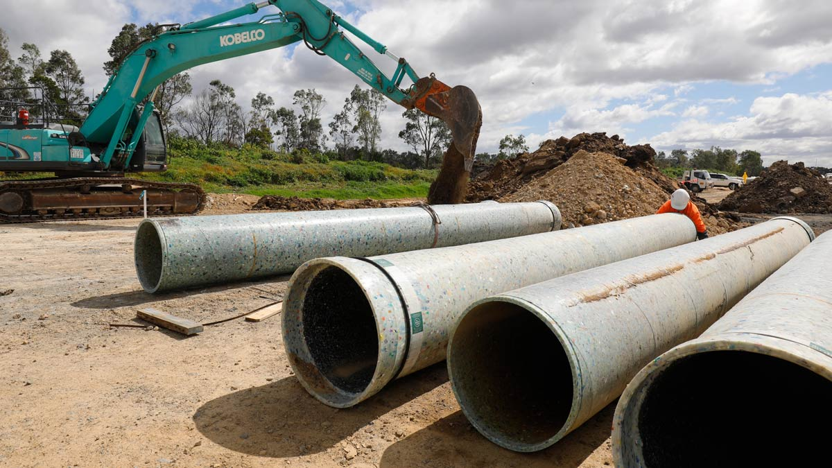 A worker in a high-vis vest inspects a pipe made from recycled plastic.