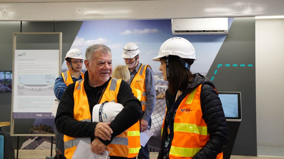 Several members of the West Gate Tunnel Project Community Liaison Group wear hard hats and high-vis vests, standing in front of project posters and touchscreens.
