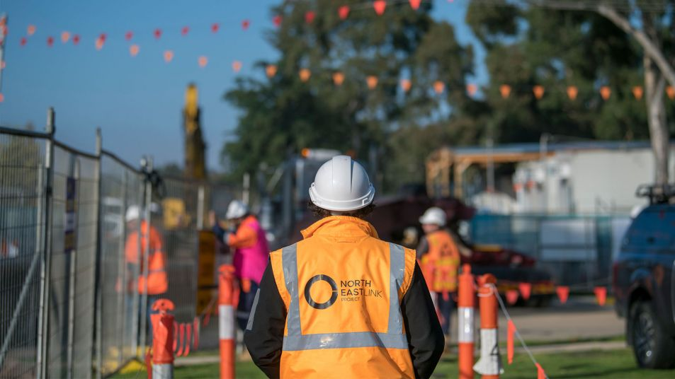 A construction worker wearing a high-vis jacket with the North East Link Project logo and hard hat. They are standing in the foreground with their back to camera looking at other workers on a construction site.
