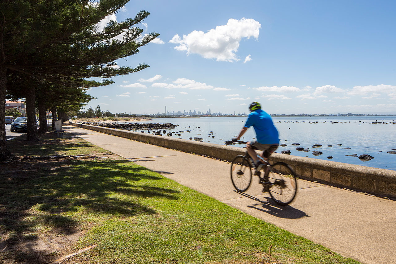 A cyclist riding on the esplanade at Altona with views of the city in the distance