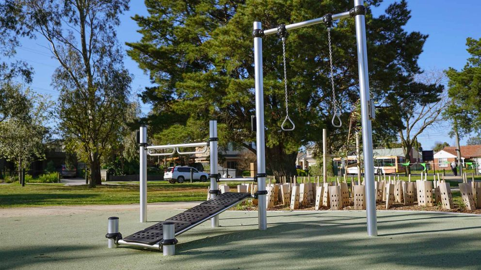 Outdoor fitness exercise station at Ford Park featuring a sit up bench, pull up rings and bar equipment.