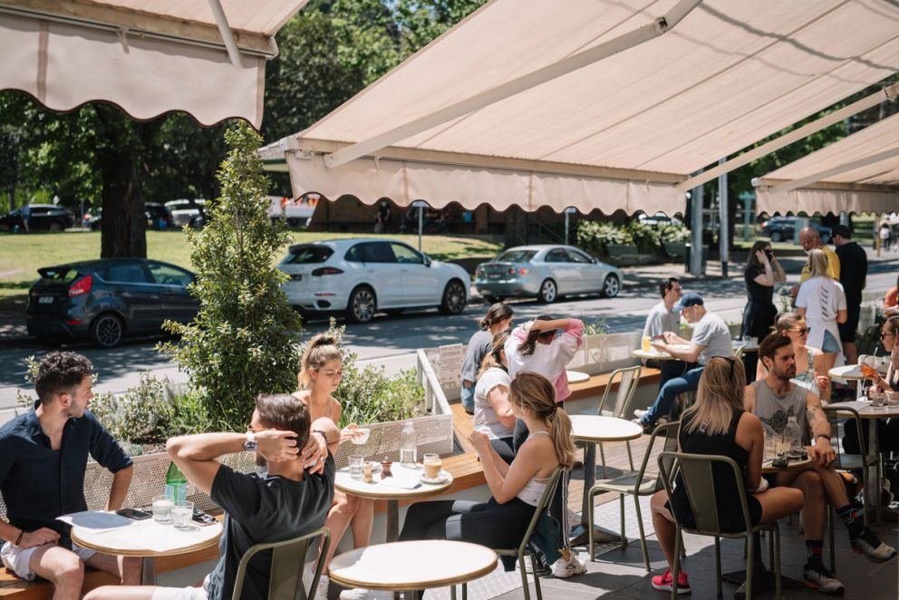 Cafe diners enjoying the outdoor seating at the popup park beside the road