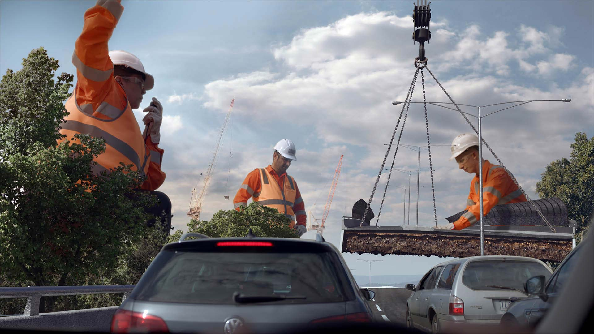 Three giant workers in hi-viz clothes and hard-hats supervise a section of road being lowered into place by a crane. Several cars wait in the foreground.
