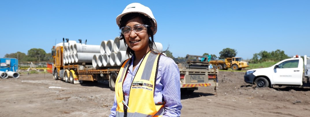 Woman in hard hat smiling at the camera on site