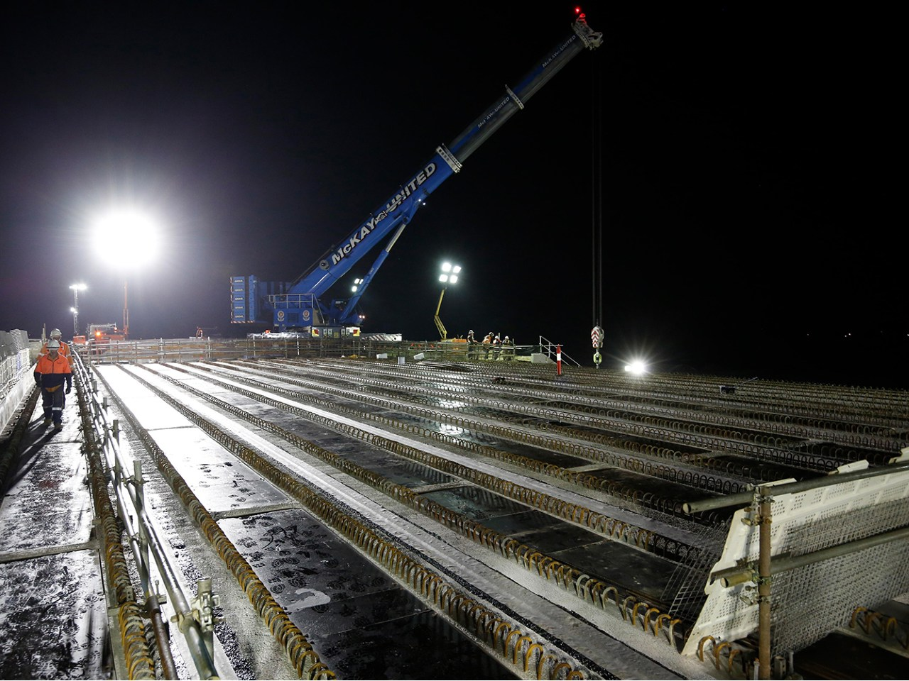 All beams are placed on top of the piers. The beams are then joined with concrete to create a bridge deck, providing the foundation for the new road
