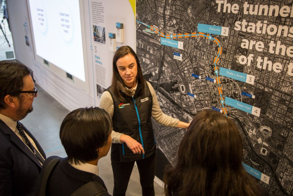 Woman taklking to people and pointing to an information board