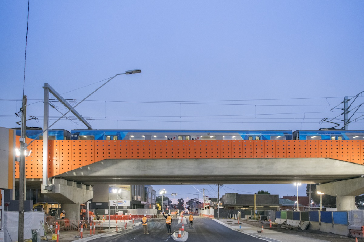 Train passes over elevated rail line at Bell St