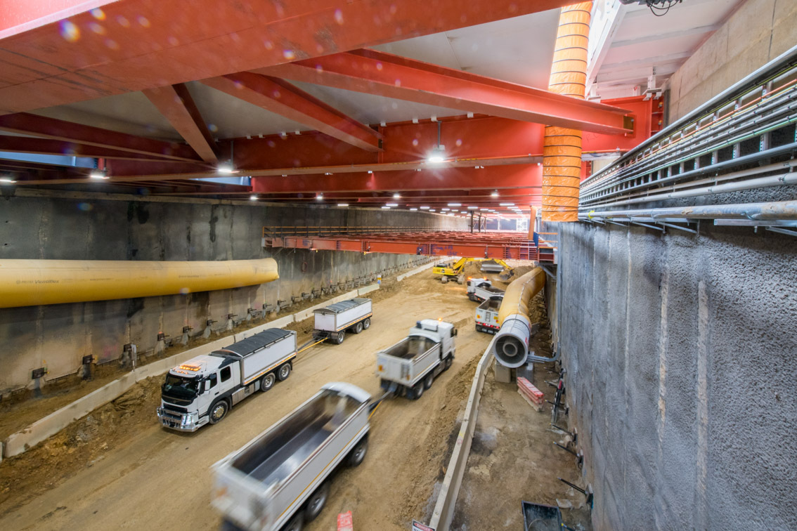 Trucks drive through a large underground construction site.