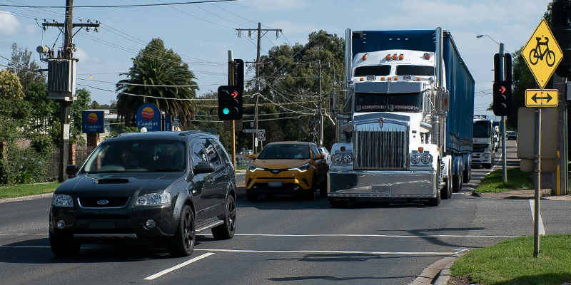 Vehicles including a truck on road travelling through intersection with a set of traffic lights
