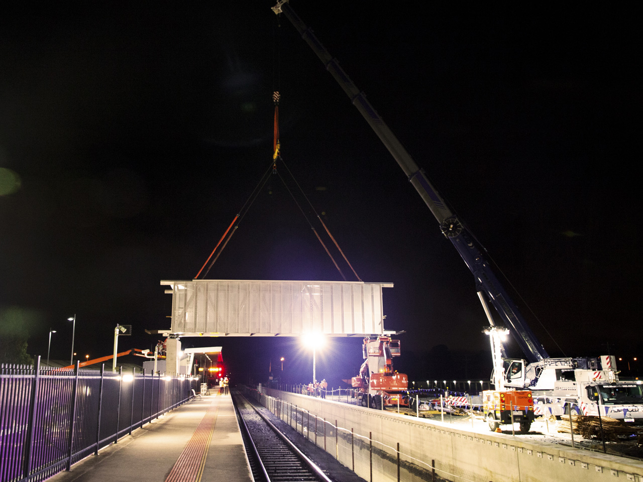 Station overpass being lifted into position at night